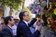El presidente de la Diputación Provincial de Huelva, Ignacio Caraballo, entrega un ramo de flores al Simpecado de la Hermandad de Emigrantes en la puerta de la Diputación.