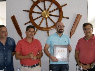 El gerente del Sol y Mar sostiene el distintivo junto autoridades organizadoras de la ruta
