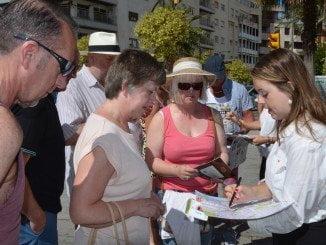 Cruceristas atienden las explicaciones para llegar al centro de Huelva