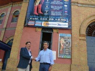 Representante de Mariscos Méndez y Carlos Pereda ante el cartel de la Feria taurina de este año