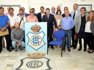 Foto histórica. Los asistentes y algunos miembros del Consejo de Administración nuevo decidieron volver a colocar el escudo histórico del Recre y una silla vacía en representación de todos los aficionados.