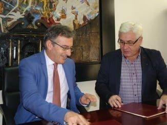 El rector y el residente del Consejo Social de la Onubense estampan su firma en el documento de acuerdo para la celebración de dos importantes enventos