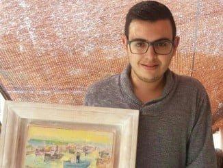 El joven isleño Emilio Jesús López Maestre muestra el cuadro que será subastado