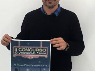 El concejal de Comercio, Carlos Guarch muestra el Cartel del Concurso