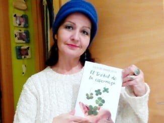 La presidenta de la Asociación FibrOnuba, Mamen Zapata, con un ejemplar de 'El trébol de la esperanza'
