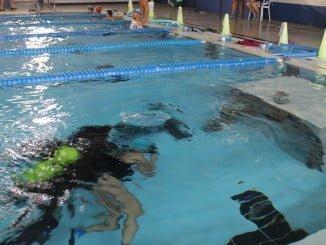 Los niños bajan a una profundidad de un metro debajo del agua, acompañado por un buceador