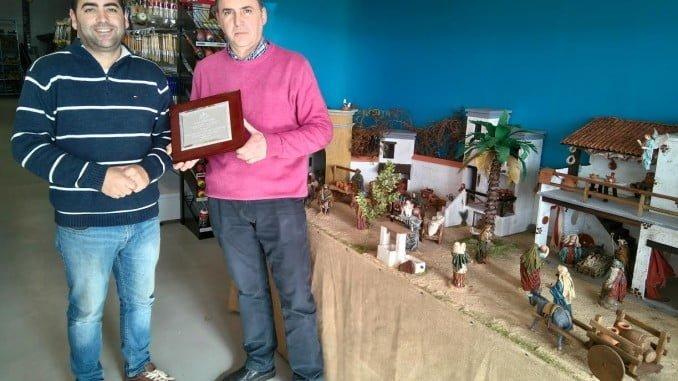 El ganador recibe el galardón de manos del presidente  de la Asociación de Empresarios de Aracena, Emilio Barrutieta, a la derecha de la imagen.