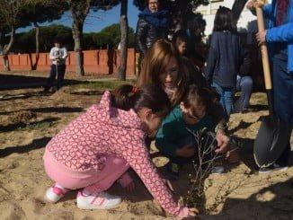 La delegada de Medio Ambiente ayuda a una alumna en la plantación de un árbol