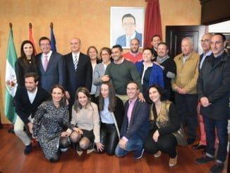 Manuel Andrés González, junto a compañeros y amigos, posando ante su retrato