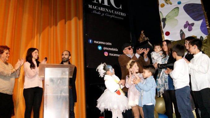 Juan Cárdenas muestra el galardón en presencia de la alcaldesa, la presidenta de la ACI y el autor y sus nietos