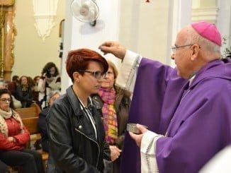El obispo de Huelva impone la ceniza a una joven durante la misa en la Catedral