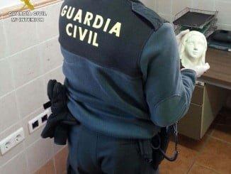 Un agente de la Guardia Civil con la cabeza de la Virgen de Lourdes tras ser recuperada