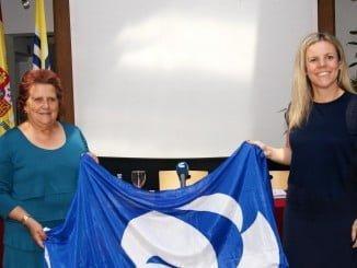 Antonia Grao y Montserrat Márquez sostienen la bandera  que  ondearၠen las dos playas isleñas