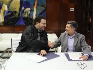Los presidentes del Puerto y de la Fundación Prenautra, rubrican el acuerdo con un apretón de manos