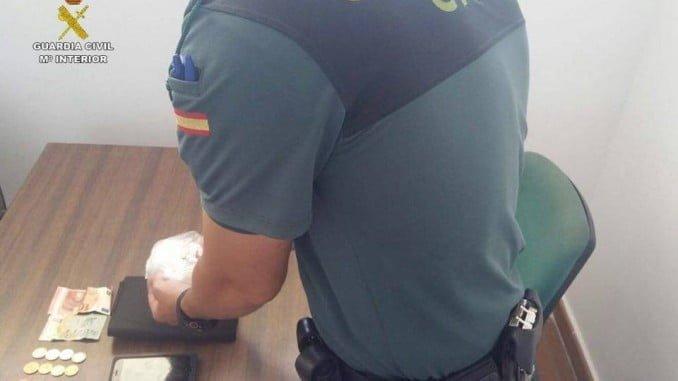 Un agente de la Guardia Civil junto a la droga incautada en Matalascañas