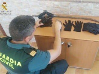 Un agente con algunos de los objetos interceptados a los detenidos