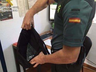 Un agente de la Guardia Civil con el bolso incautado a los presuntos ladrones