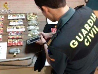 Un agente de la Guardia Civil con lo incautado a los dos menores detenidos en Cala