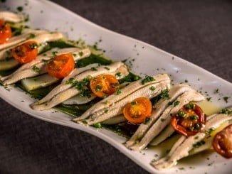 En el restaurante los Montes de Galicia nos proponenlas Anchoas marinadas y tomate cherry confitados, aliñados con aceite virgen de alberquina, un plato que contiene algunos de los alimentos imprescindibles para este verano