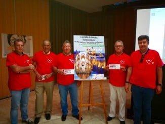 Miembros de la asociación onubense, junto al cartel del encuentro.