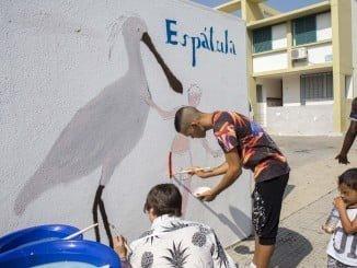 Niños decorando los muretes de la barriada