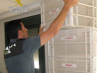 Un agente de la Guardia Civil con algunas de las cajas recuperadas