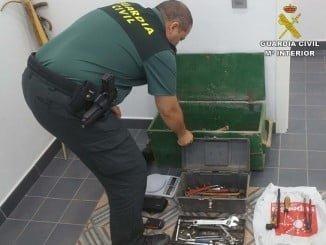 Un agente de la Guardia Civil con algunos de los objetos encontrados en el vehículo