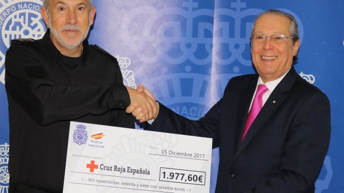 El comisario jefe entrega al presidente de Cruz Roja el cheque de la carrera solidaria.