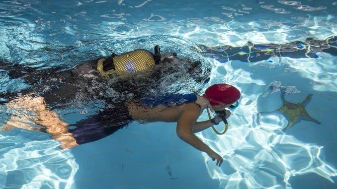 Un buzo de Bomberos guía a un niño para ver el belén acuático