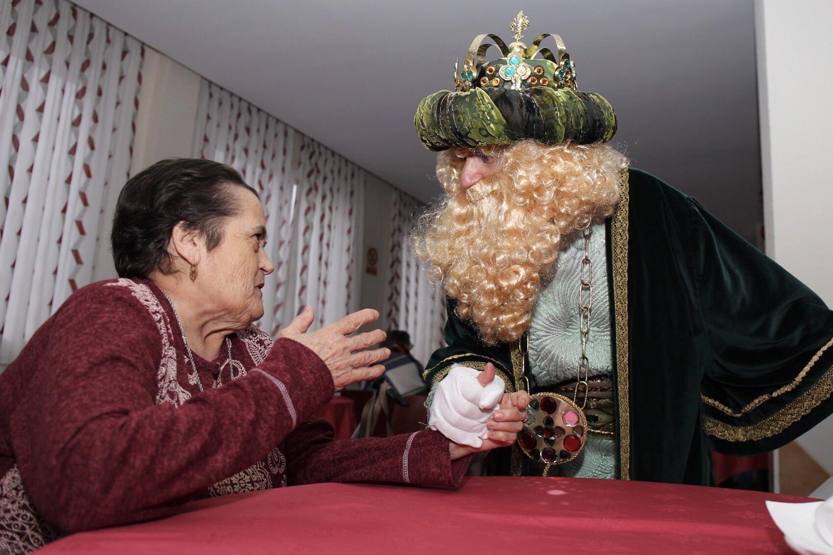 El Rey Gaspar conversa con un mayor en una de las residencias visitadas
